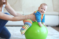 Baby gymnastic. Baby playing with gymnastic ball with mother at home Stock Image