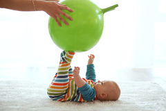 Baby gymnastic. Baby playing with gymnastic ball with mother at home Stock Photos