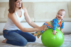 Baby gymnastic. Baby playing with gymnastic ball with mother at home Stock Photography