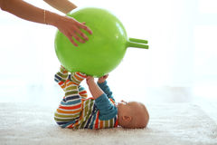 Baby gymnastic. Baby playing with gymnastic ball with mother at home Royalty Free Stock Photography