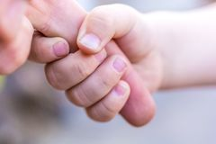 Baby h?lt Finger seines stolzen Vaters lizenzfreie stockfotografie