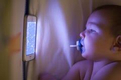 Baby hållande ögonen på tecknade filmer för en vaggvisa med mobiltelefonen på lathunden Royaltyfria Foton