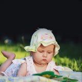 Baby håller ögonen på en bok Arkivfoto