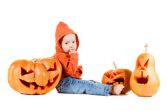 Baby and Halloveen pumpkins with a grimace on white background Royalty Free Stock Photography
