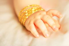 Baby hand. With yellow gold bracelets,  towards white silk Royalty Free Stock Images