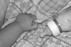 Baby Hand. Close up of a baby hand on a blanket with a bottle Royalty Free Stock Photo