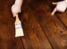 Baby hand applying protective varnish on a wooden table Royalty Free Stock Photo