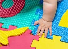 Baby-Hand auf dem Boden Stockfotos