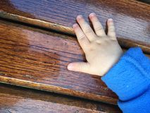 Baby hand on a bench Royalty Free Stock Images