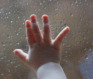Baby hand against a window in the rain. Baby hand against a glass window with raindrops Royalty Free Stock Image