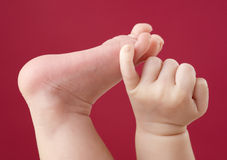 Baby hand and foot. Close-up on baby foot and hand on red background Stock Photos