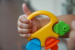 Baby hand with good sign. Baby holdings his colorful toy, thumb up as good sign Royalty Free Stock Images