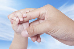 Baby hand grasping father finger Stock Photos