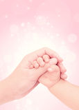 Baby hand in hand of love. With pink glitter background Stock Photos