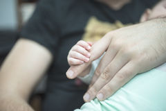 Baby hand holding adult finger Stock Images