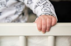 Baby hand holding bed edge. Closeup infant body part Royalty Free Stock Photo