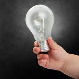 Baby hand holding light bulb. Royalty Free Stock Photography