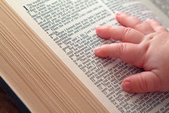 """Baby Hand on Open Bible. Baby hand on Jeremiah Bible verse """"Be not afraid Stock Image"""