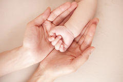 Baby hand in mother's palm Stock Photos