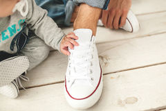 Baby hand on the shoe of the father close-up Stock Photos