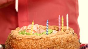 Baby handles decorate a cake with candles stock video footage