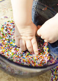 Baby hands in a bowl of sprinkles. Baby hands playing in a bowl of sprinkles Stock Photo