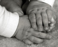 Baby hands and feet. Baby hands playing with feet on top of fluffy blanket in monochrome royalty free stock photos