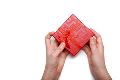 Baby hands holding a red gift box isolated on a white background. Top view Royalty Free Stock Images