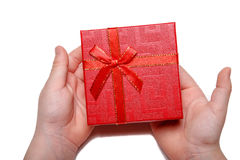 Baby hands holding a red gift box isolated on a white background. Top view Stock Image