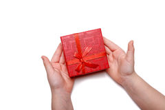 Baby hands holding a red gift box isolated on a white background. Top view Royalty Free Stock Image