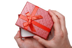 Baby hands holding a red gift box isolated on a white background. Top view Stock Photos