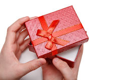 Baby hands holding a red gift box isolated on a white background. Top view Stock Photography