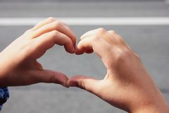 Hands folded heart. The concept of peace, friendship and love stock photo
