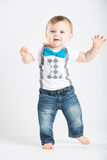 Baby with Hands Out Dancing. A cute 1 year old stands in a white studio setting. The boy has a happy expression with his hands out. He is dressed in Tshirt Royalty Free Stock Photo
