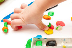 Baby hands with plasticine. Child moulds from plasticine on table Stock Image
