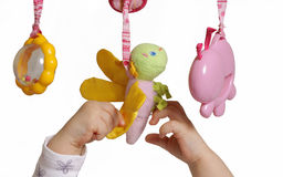 Baby hands with toys. Baby hands playing with toys, isolated on white stock image