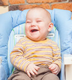 A baby happiness sitting on high chair Stock Photos