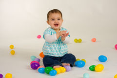 Baby Happy about Easter Eggs. Cute baby girl with easter plastic eggs royalty free stock photos