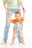Baby happy go first steps. Mother helping child. Stand, white background Royalty Free Stock Photos