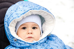 Baby happy laughing enjoying a walk in a snowy winter park sitting in a warm stroller with sheepskin hood. Happy laughing baby girl enjoying a walk in snowy Royalty Free Stock Images