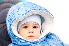 Baby happy laughing enjoying a walk in a snowy winter park sitting in a warm stroller with sheepskin hood. Happy laughing baby girl enjoying a walk in snowy Stock Images