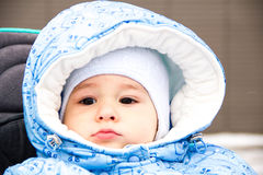 Baby happy laughing enjoying a walk in a snowy winter park sitting in a warm stroller with sheepskin hood. Happy laughing baby girl enjoying a walk in snowy Stock Image