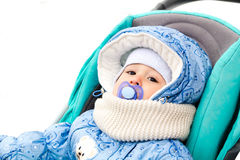 Baby happy laughing enjoying a walk in a snowy winter park sitting in a warm stroller with sheepskin hood. Happy laughing baby girl enjoying a walk in snowy Royalty Free Stock Photos