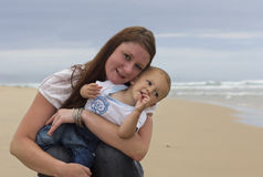 Baby boy with happy mother on beach, smile Stock Photo