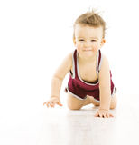 Baby happy smiling with uncombed hairs, active tousled boy in sp. Ort suit crawling isolated over white background Stock Photo