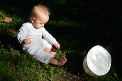 Baby and a hard cap on the ground Royalty Free Stock Photos