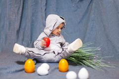 Baby in hare jumpsuit and easter eggs stock photography