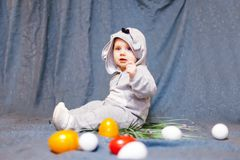 Baby in hare jumpsuit and easter eggs. Baby in rabbit costume and with Easter eggs royalty free stock image
