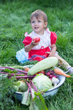 Baby with the harvest of vegetables. In the garden Royalty Free Stock Image