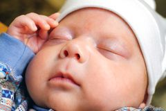 The baby has a Cap on his head, he sleeps peacefully stock photo